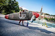An Aare swimmer is getting ready to enter the river Aare with a surfboard and three waterproof floating Aare bags as company. The Aare river floats right through the Swiss capital Bern, and as soon as the temperature crawls above 10 degrees, people are seen jumping in the water for a swim. Many use the river regularly to swim to lunch or to and from work. Some even swim year round.