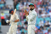 Virat Kohli (captain) of India with Alastair Cook of England in the background during day 3 of the 5th test match of the International Test Match 2018 match between England and India at the Oval, London, United Kingdom on 9 September 2018.