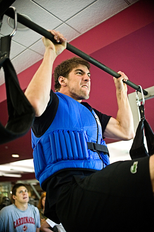 Freelance photo by Matt Roth.Baltimore, Maryland.Thursday, May 7, 2009.Assignment ID: 20102758A..Pull ups are more difficult for Olympian Michael Phelps with a 45 lbs. weight vest. After a low energy Thursday practice in the water, members of the North Baltimore Aquatic Club lift weights at the Loyola College Aquatic Center's weight room in Baltimore, May 7, 2009.