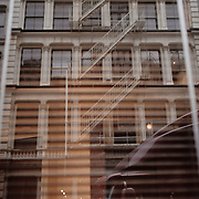 Reflection of a brownstone in the window in Soho