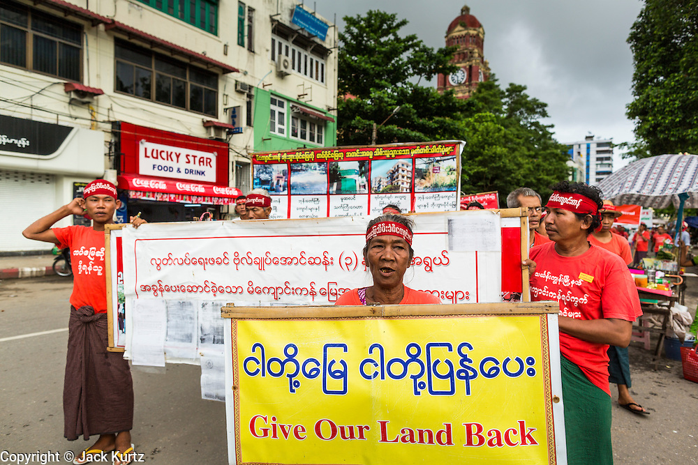 07 JUNE 2014 - YANGON, MYANMAR: Burmese peasants who say their land was misappropriated by the Burmese army march in central Yangon. About 100 Burmese citizens who say they've lost their land to the Burmese army, had a protest march in central Yangon Saturday. It's a sign of how quickly Myanmar is changing that authorities allowed the march, and other protests like it, to proceed without interference.   PHOTO BY JACK KURTZ