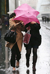 Office workers scamper for cover as torrential rain and  strong winds hit London, Wednesday, 12th February 2014. Picture by Stephen Lock / i-Images