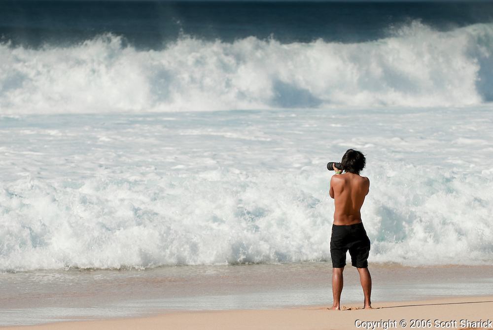 A man photographs the waves on the North Shore of Oahu, Hawaii.
