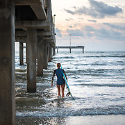 Surfer girl is walking into the water carrying a surfboard.