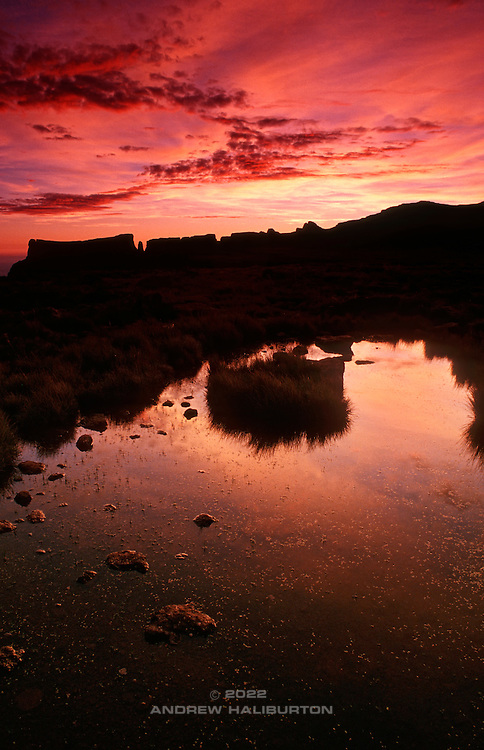 Red dawn and reflection in a wetland marsh near Tugela Falls on the Amphitheatre summit plateau.  In profile, left to right are Eastern Buttress 3047m, Devil's Tooth, Inner Tower and Mount Oompie. Ukhahlamba-Drakensberg Park, KwaZulu-Natal, South Africa.  Nikon F90, 24/2.8D. E100SW. December 1996.