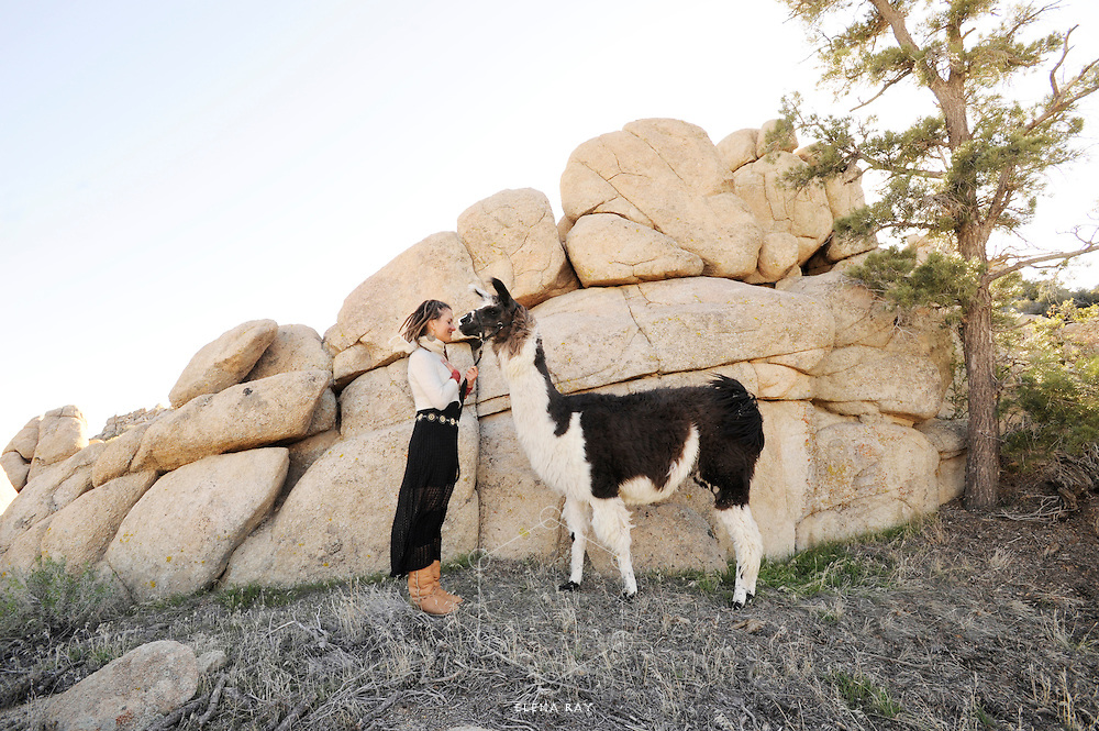 A woman and her beloved Llama friend, outdoors in nature.