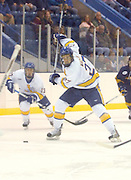 Lake Superiior State University's Zac MacVoy (27) winds up for a shot on Canisius Griffins goaltender (out of frame left) Dan Morrison as teammate Fred Cassiani (13) looks on during the second period of the Lakers Saturday night game against the Griffins.