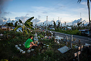 A woman poses flowers on a relative's grave at a mass grave improvised in a roundabout on June 15 2014 in Palo, Philippines. Tacloban city and the surrounding villages were devastated after typhoon Hayan passed over leaving at least 6,200 people dead and a high number of disappeared on November 8, 2013.