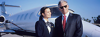 Businessman and Flight Crew Standing by Airplane