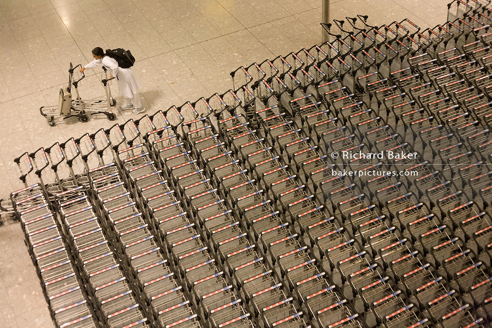 "Seen from an aerial walkway, we look down on a lady airline passengers struggling to separate two trolleys in the baggage reclaim hall in the arrivals of Heathrow Airport's Terminal 5. 50-70,000 pieces of British Airways baggage a day travel through 11 miles of conveyor belts which were installed in a 5-storey underground hall beneath the 400m (a quarter of a mile) length of Terminal 5. T5 alone has the capacity to serve around 30 million passengers a year and was completed in 2008 at a cost of £4.3bn. The system was designed by an integrated team from the airport operator BAA, BA and Vanderlande Industries of the Netherlands, and handles both intra-terminal and inter-terminal luggage. From writer Alain de Botton's book project ""A Week at the Airport: A Heathrow Diary"" (2009)."