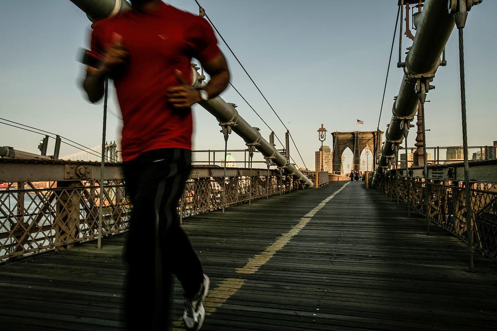 Runner passing in Brooklyn bridge in New York.