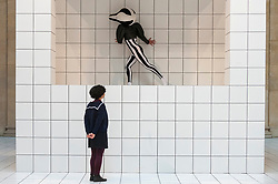 """© Licensed to London News Pictures. 21/03/2018. LONDON, UK. A woman looks at a performer wearing a squash-like costume the preview of """"The Squash"""", an immersive installation combining performance and sculpture by 2016 Turner Prize nominee Anthea Hamilton.  At Tate Britain, performers will wear outfits from a collection of seven elaborate squash-like costumes to showcase Hamilton's work amidst 7,000 white floor tiles spanning the entire Duveen Galleries and Tate Britain's own sculpture collection.  The show runs 22 March to 7 October 2018.  Photo credit: Stephen Chung/LNP"""