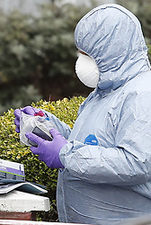 © Licensed to London News Pictures. 03/04/2018. London, UK.  A police forensics officer is seen putting mobile phones in a bag at the scene in Chalgrove Road, Tottenham, north London where a 17 year old girl was shot dead. The girl was found with a bullet wound and pronounced dead at the scene at 21:43 last night. Police were also called to another shooting and stabbing incident in Walthamstow. Photo credit: Peter Macdiarmid/LNP