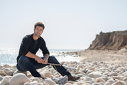 hot man sitting on a rocky beach