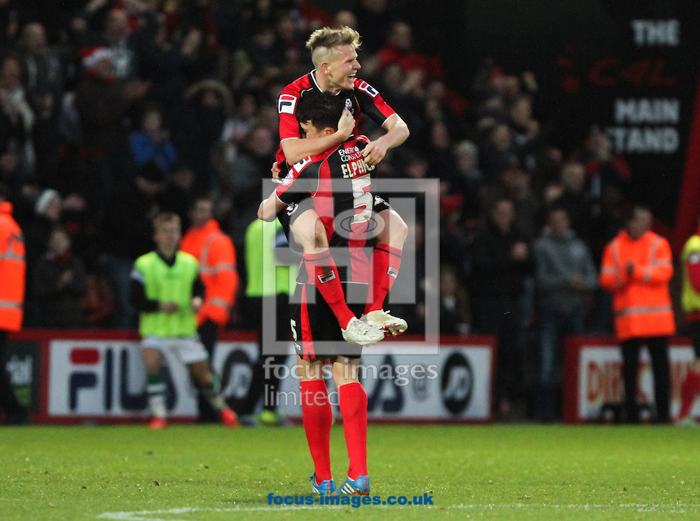 Picture by Tom Smith/Focus Images Ltd 07545141164<br /> 26/12/2013<br /> Matt Ritchie (back centre) of Bournemouth jumps onto Tommy Elphick (front centre) in celebration of scoring the goal to make it 2-0 to his side during the Sky Bet Championship match at the Goldsands Stadium, Bournemouth.