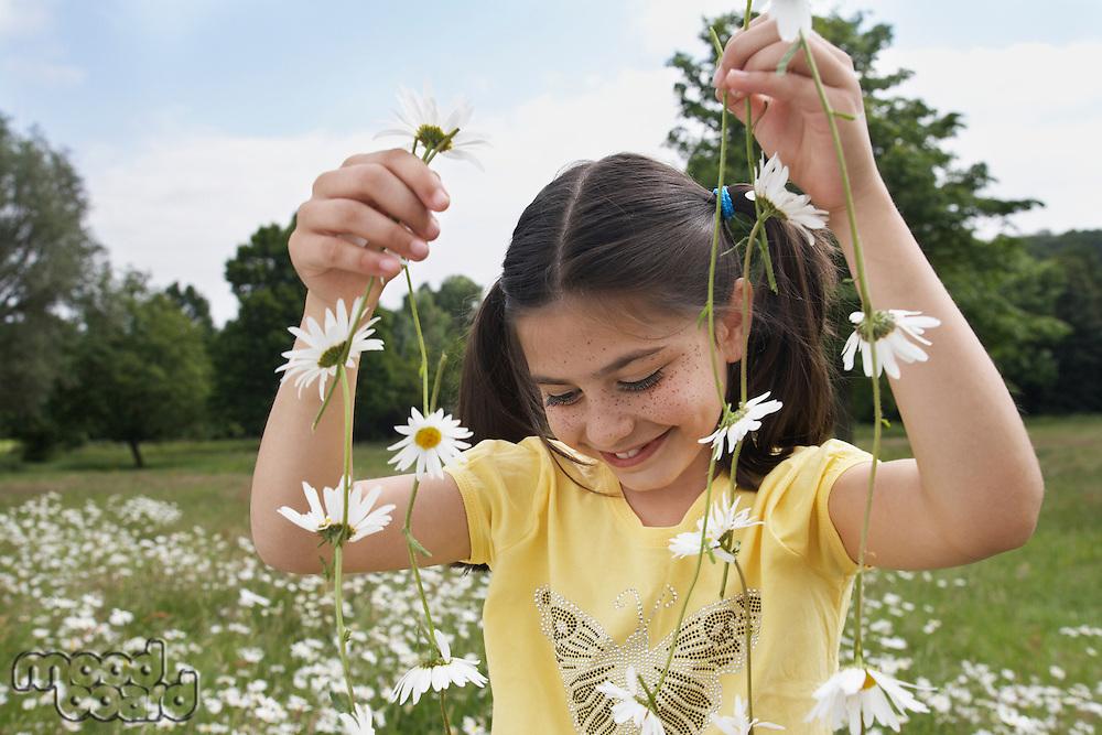 Girl (7-9) holding flowers in meadow