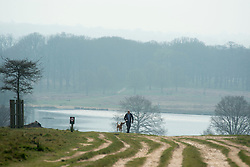 © Licensed to London News Pictures. 02/04/2014. Richmond, UK. A man walks a dog up a hill.  Visitors to Richmond Park had low visibility today April 2nd 2013. High levels of air pollution are set to spread across England and are expected  to get worse. Photo credit : Stephen Simpson/LNP