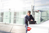 Attractive mature businessman putting his luggage on car trunk