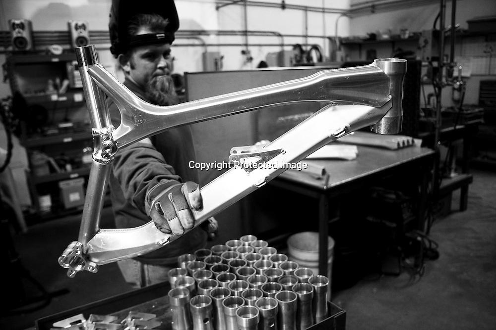 A welder displays his work- an aluminum mountain bike frames handmade in Intense's Temecula, California factory. Intense Cycle's 951 downhill mountain bike manufacturing line tour.