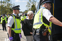 London, UK. 4 September, 2019. Metropolitan Police officers arrest an anti-nuclear activist who had locked herself to another activist using an arm tube to block one of the two main access roads to ExCel London during protests on the third day of a week-long carnival of resistance against DSEI, the world's largest arms fair. The third day's protests were organised by the Campaign for Nuclear Disarmament (CND) and Trident Ploughshares.