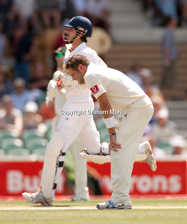 Bowler Ryan Harris feels the heat as Alastair Cook runs past during the second Ashes Test Match between Australia and England at the Adelaide Oval. Photo: Graham Morris (Tel: +44(0)20 8969 4192 Email: sales@cricketpix.com) 4/12/10