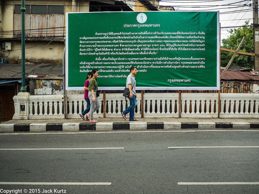 11 OCTOBER 2015 - BANGKOK, THAILAND:  People walk past a government posting announcing the closing of Saphan Lek and Saphan Han markets in Bangkok. The two markets are across the street from each other Many shops in the markets are already closed. Street vendors and illegal market vendors in the Saphan Lek and Saphan Han will be removed in the next two weeks as a part of an urban renewal project coordinated by the Bangkok Metropolitan Administration. About 500 vendors along Damrongsathit Bridge, popularly known as Saphan Lek, have until Monday, October 11,  to relocate. Vendors who don't move will be evicted. Saphan Lek is one of several markets and street vending areas being closed in Bangkok this year. The market is known for toy and replica guns, bootleg and pirated DVDs and CDs and electronic toys.   PHOTO BY JACK KURTZ