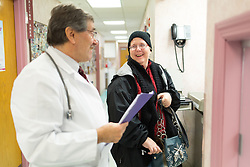 1/27/15 10:21:24 AM -- Louisa, KY, U.S.A  -- Cheryl Castle, left, talks to her son Nate's pediatrician Dr. Mazen Jaafar who was seeing Nate for a low grade fever and cough. Cheryl is a recent recipient of the high-tech device, can now do many tasks she was unable to do when her epileptic seizures became more severe and more frequent. Now she's getting back to a normal life.<br /> <br />  --    Photo by Jonathan Palmer, Freelance