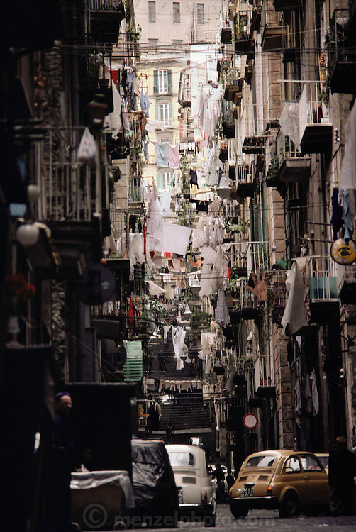 Laundry hanging on balconies and across a narrow street in Naples, Italy.