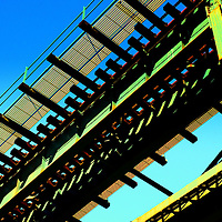 Rusty, old subway bridge against blue sky from a low angle, Bronx, New York City