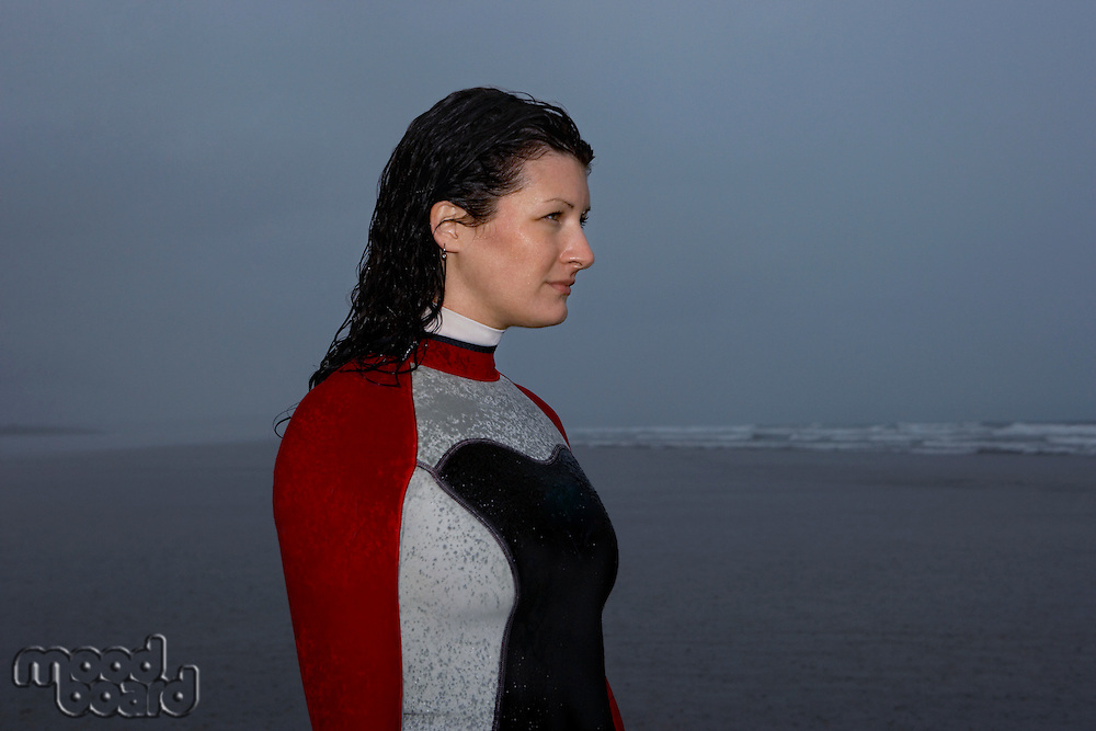 Female surfer standing in shallow water looking at sea at dusk side view
