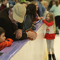 Mike Smith and his grandson Lake Slagowitz,6, watch the ice skaters Saturday at the Bancorpsouth Arena