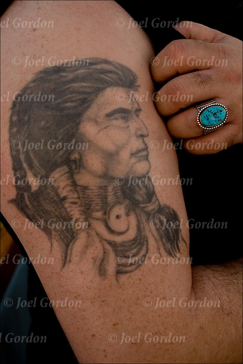 Native American tattoo on right arm of Native American at pow wow.