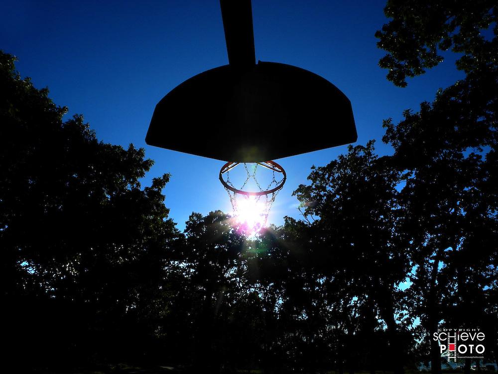 Basketball hoop in late afternoon sun.