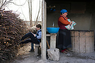 Ana Sabashvili bakes loaves of bread in a traditional woodfired oven on the compound of the displacement camp where she lives in Berbuki, Georgia. Her family, including her son Giorgi (left) fled war in South Ossetia in 2008, and have lived at the displacement camp for nine years. (photo by Claire Harbage)