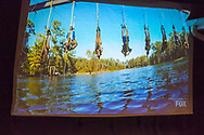 "Merrick, New York, USA. 11th June 2017.  During ""American Grit"" Season 2 premiere, (2nd from right in blue swim trunks) CHRIS EDOM, 48, of Merrick, is one of 17 contestants suspended from beams above lake water during an endurance challenge. Show was projected on large screen during Edom's backyard Viewing Party for Episode 1 of FOX network reality television series. Edom was last contestant picked for a team that episode."