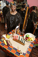Gaile McLemore, owner of Cachet G in downtown Dayton in African dress with items (on the table) that would make appropriate gifts for Kwanzaa, Tuesday, December 20, 2011.