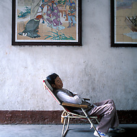 China, Sichuan Province, Fengjie, Man naps inside entrance to Baidicheng, The White Emperor's Palace along Yangtze River.