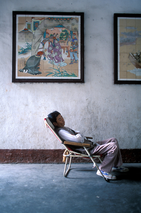 China, Sichuan Province, Fengjie, Man naps inside entrance to Baidicheng, The White Emperor's Palace along Yangtze River.
