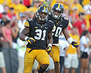 August 31 2013: Iowa Hawkeyes linebacker Anthony Hitchens (31) and Iowa Hawkeyes linebacker Christian Kirksey (20) celebrate after a stop during the second half of the NCAA football game between the Northern Illinois Huskies and the Iowa Hawkeyes at Kinnick Stadium in Iowa City, Iowa on August 31, 2013. Northern Illinois defeated Iowa 30-27.