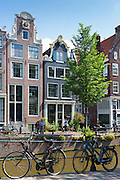 Cyclists, bicycles and canalside gabled houses - Dutch gables on Brouwersgracht in Amsterdam, Holland