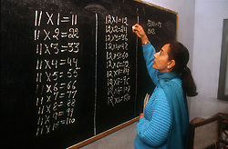 Female teacher writing arithmetic tables on the blackboard in senior secondary modern school; Punjabi University; Patiala; Punjab; India,