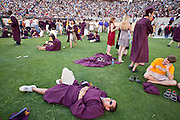 13 MAY 2009 -- TEMPE, AZ: David Cousino (CQ) a marketing grad from Ohio, lays on the grass during the heat at graduation. President Barack Obama addressed the Arizona State University class of 2009 during the commencement program in Sun Devil Stadium in Tempe Wednesday evening.  PHOTO BY JACK KURTZ