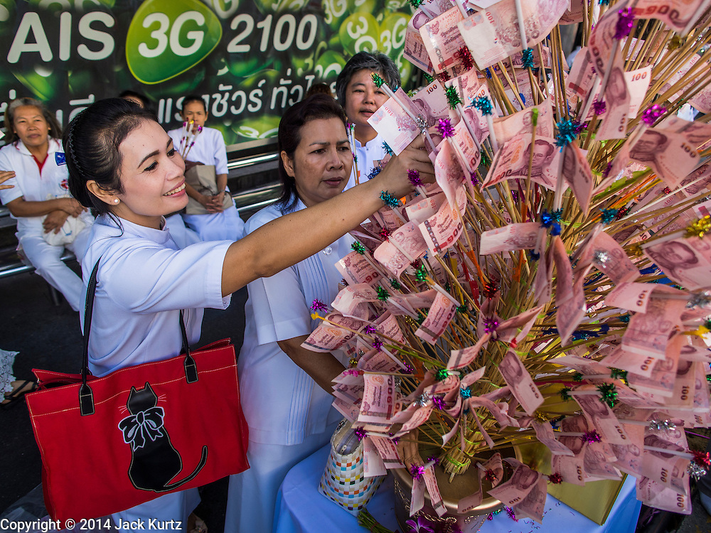 23 NOVEMBER 2014 - BANGKOK, THAILAND: A woman places monetary donations into a money tree at a mass alms giving ceremony in Bangkok Sunday. 10,000 Buddhist monks participated in the ceremony on Rajadamri Road in front of Central World shopping mall. The alms giving was to assist Buddhist temples in the insurgency wracked southern provinces of Thailand, where Buddhist monks on their alms rounds have been targeted by Muslim extremists. The ceremony was sponsored by Wat Phra Dhammakaya, the center of the Dhammakaya Movement, a Buddhist sect founded in the 1970s. The temple has become active in Thai politics.    PHOTO BY JACK KURTZ