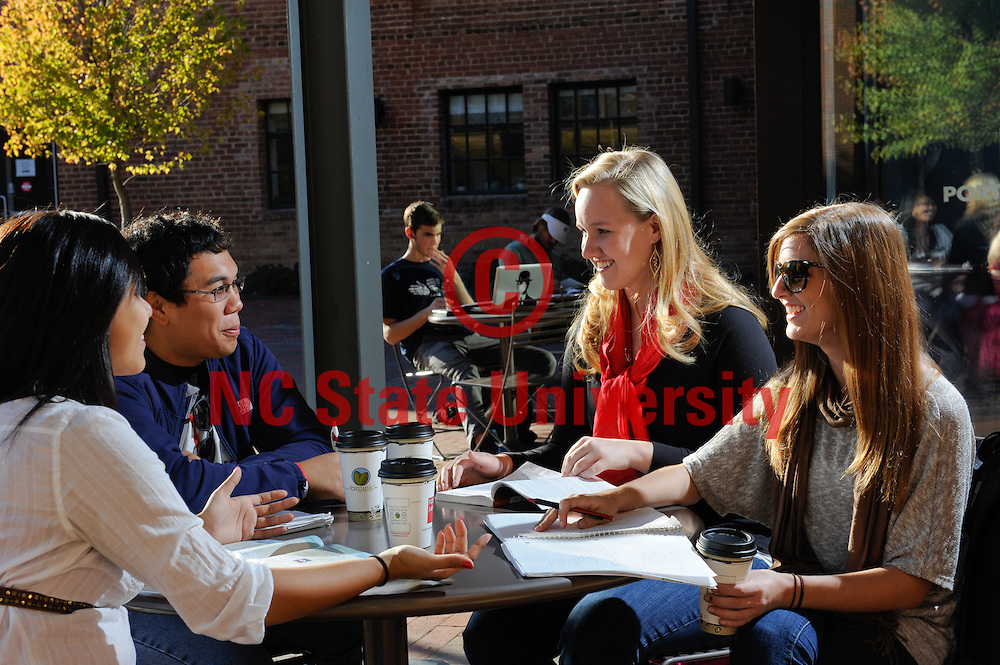 Students share conversation while sitting in front of the Port City Java near SAS Hall. Photo by Marc Hall.