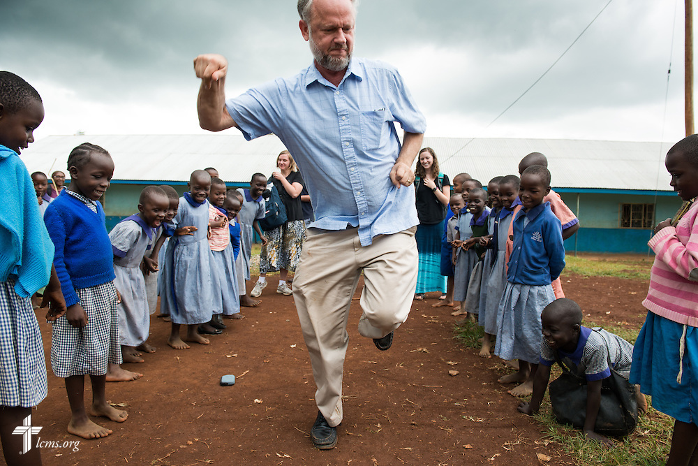 The Rev. Dr. John Juedes, pastor of Messiah Lutheran Church in Highland, Calif., plays hopscotch with children after arriving Monday, June 9, 2014, at the Luanda Doho Primary School in Kakmega County, Kenya. Juedes is part of a 14-member Mercy Medical Team using a part of the school for a week-long medical clinic. LCMS Communications/Erik M. Lunsford