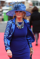 © Licensed to London News Pictures. 08/04/2016. Liverpool, UK. A lady wearing a striking blue dress and matching hat arrives at the Grand National 2016 for Ladies Day at Aintree Racecourse near Liverpool. The race, which was first run in 1839, is the most valuable jump race in Europe. Photo credit : Ian Hinchliffe/LNP