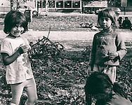 Three Roma kids playing with fresly cut grass around the Sarajevo railway station.
