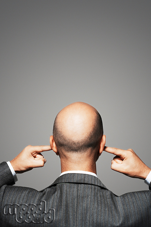 Balding businessman with fingers in ears back view
