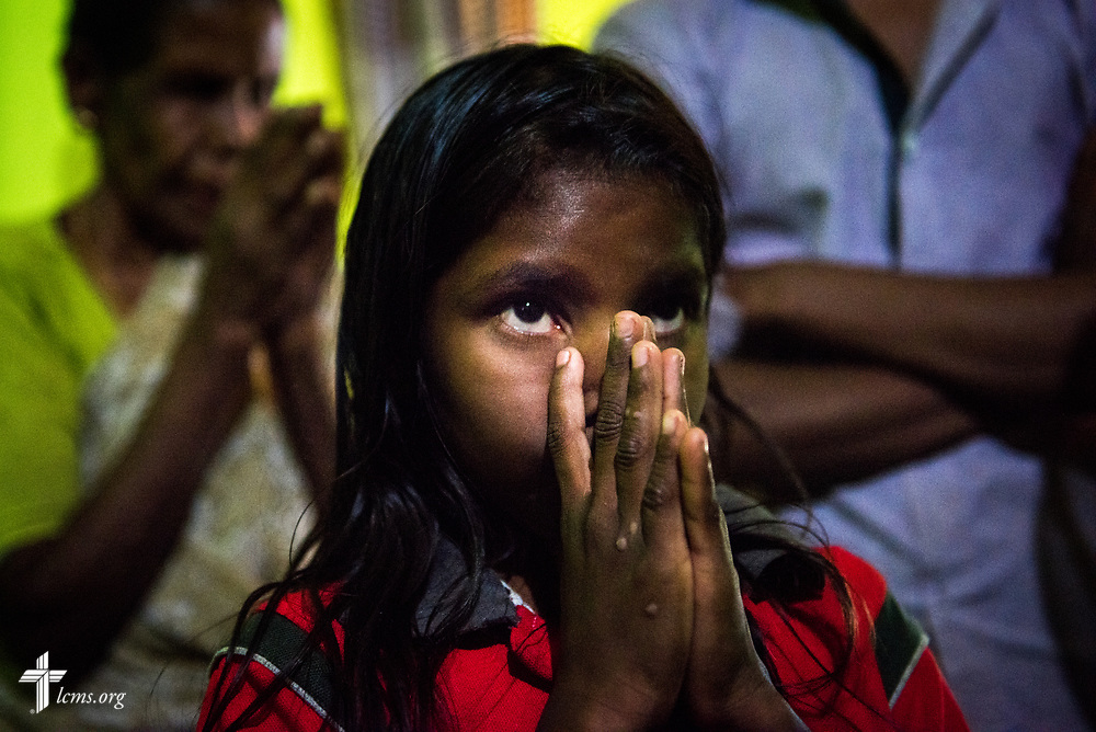 A young girl in a home on the Eila rubber plantation in the Sabaragamuwa Province of Sri Lanka prays with the Rev. P. Gnanakumar, and the Rev. Steven Mahlburg, LCMS career missionary to Sri Lanka (both not pictured), during a visitation on Saturday, Jan. 20, 2018. LCMS Communications/ Erik M. Lunsford
