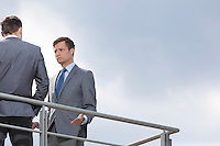 Serious businessman looking at coworker against clear sky